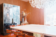 Orange leather chairs and a white marble table atop orange-red carpeting