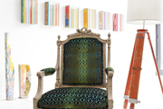 An antique French chair covered in Opuzen iridescent fabric near a tripod floor lamp