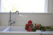 Colorful flowers contrasted against all white kitchen sink with tiled backsplash.
