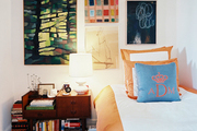 A gallery wall of art above a twin bed with a monogrammed throw pillow