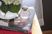 A single hydrangea and perfume bottles form the perfect bedside vignette
