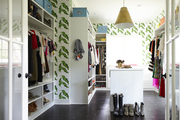 Long walk in closet with bright wallpaper and black tiled floor.