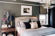 A masculine bedroom with neutral bedding and a wood bedside table