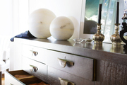 Spheres and a pair of candlesticks top a sideboard in a dining room