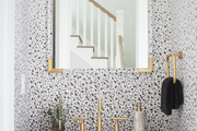A half-bathroom with speckled black and white wallpaper and gold accents.