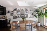 This dining area features a gallery wall and a fiddle leaf fig tree.