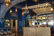 A blue-and-white ceiling treatment and gold pendant lamps in Jaipur's Bar Palladio