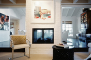 A white chair beside a two-sided painted-brick fireplace