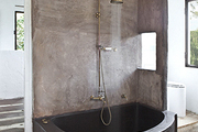 A custom concrete tub and brass shower fittings outfit a spare bathroom.