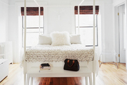 A white bench and a pair of sheepskin rugs at the foot of a white canopy bed