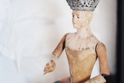 A wooden figurine wearing a crown atop a book