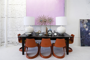 Red midcentury chairs at a table under artwork at Buckingham Interiors + Design