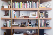 A custom-built shelving piece houses books, a record player, and assorted eclectic items