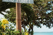 A street sign next to yellow flowers on Harbour Island