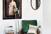 A reading nook with a vintage chair and portrait