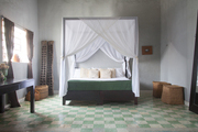A four-poster bed in a sparsely furnished room