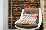 A white floor lamp and a midcentury chair beside brick walls