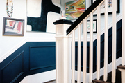 A grouping of artwork in a black-and-white stairwell