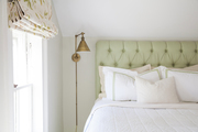 Tufted headboard behind white bedding.