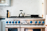 A stainless steel stove before a white tile wall.