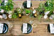 A rustic tablescape with black plates and greenery.