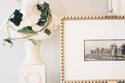 A bust and framed art on a white mantel