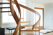 A wooden spiral staircase in a white room.