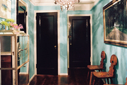 Blue walls and black doors in a hallway with a mirrored cabinet
