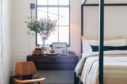 A metal canopy bed, side table, and midcentury chair