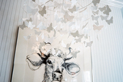 A mobile of butterflies beside a portrait of a cow