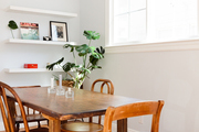 A minimalist dining room with a plant and shelf.