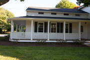 Outdoor wrap around porch and large front lawn.