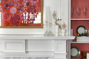 An orange-accented dining room a marble hearth and coral-backed bookcases.