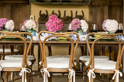 A rustic dining table topped with hydrangeas