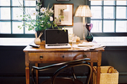 Deep-gray walls in an office space with a wooden desk and a black bentwood chair