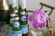 A bar cart with Pellegrino and champagne