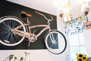 A bike hung from a wall with black paint and white tile