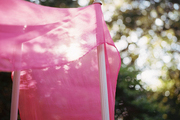 A DIY pink tent with white poles