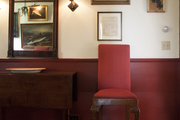 A red upholstered dining chair beside a wooden drop-leaf table