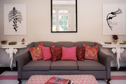 A gray couch with pink pillows atop a striped rug