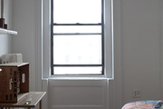 A bare window surrounded by original molding.