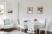 White and floral furniture beside animal fur area rug in white trimmed dining room.