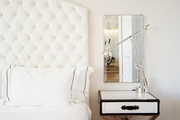 A white tufted headboard in a neutral guest room