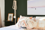 A contemporary bedroom with a green wall.