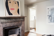 A rustic wooden mantel topped with artwork by Alex Katz