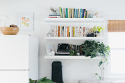 """The photographer admits few structural changes have been made to the interior of her cottage home. """"I added IKEA shelves — and plenty of plants,"""" she says. Drawing the eye up, with floating shelves like the Lack Series by IKEA, not only provides the illusion of height, but offers ample storage."""