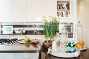 An island in an open kitchen with white cabinetry