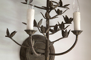 An antique iron sconce with a repeating leaf motif