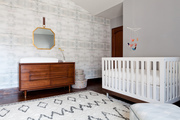 Contemporary crib and wood dresser in a gray and white nursery.