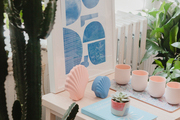 Pink and blue decor items on a light wooden table.
